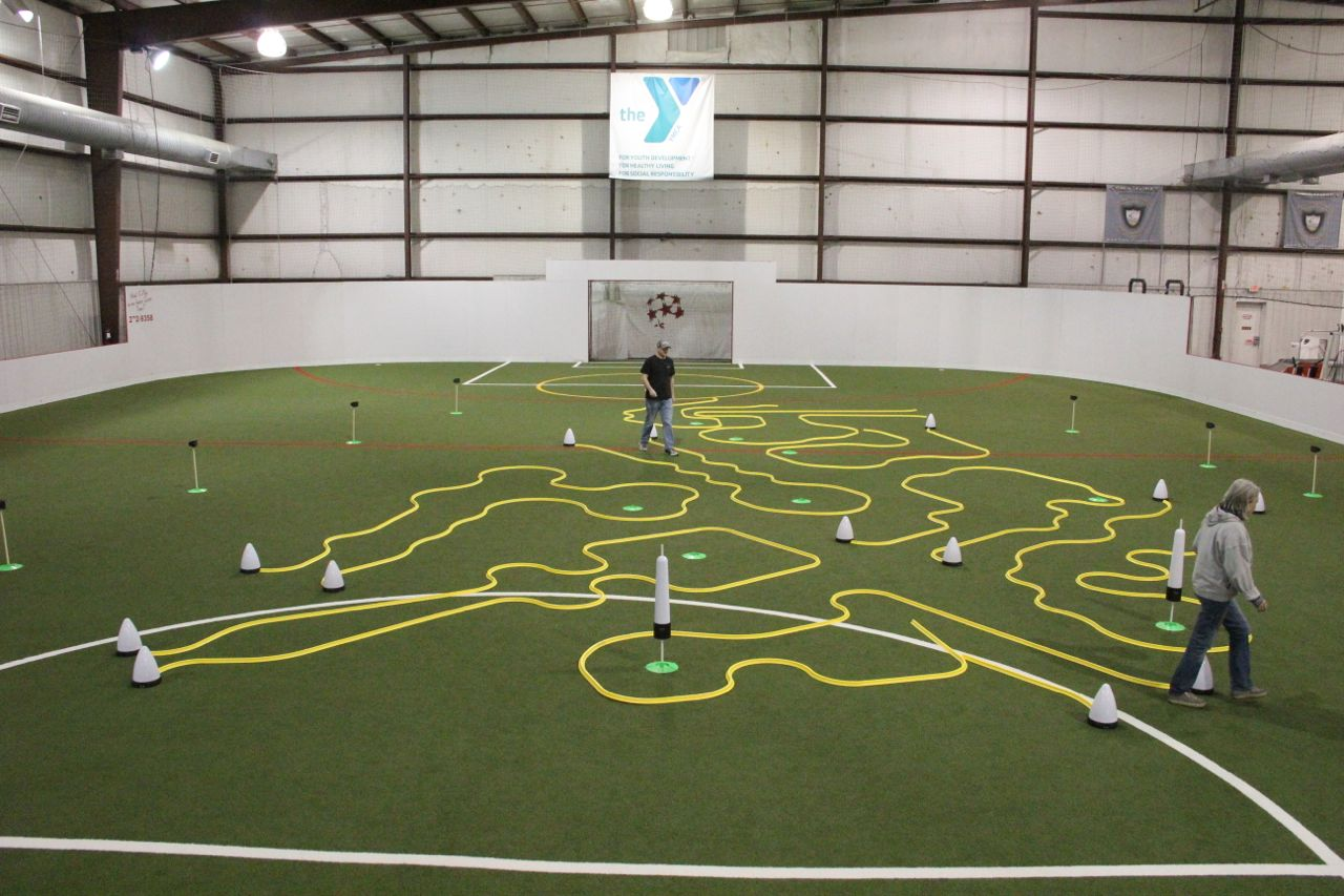 full office golf putting track set up on indoor soccer field